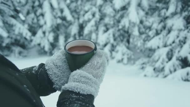 Eisentasse mit heißem Kaffee in weiblichen Händen in Strickhandschuhen vor dem Hintergrund des Nadelwaldes im Winter. Wintermärchen und eine Tasse Heißgetränk in den Händen des Mädchens.