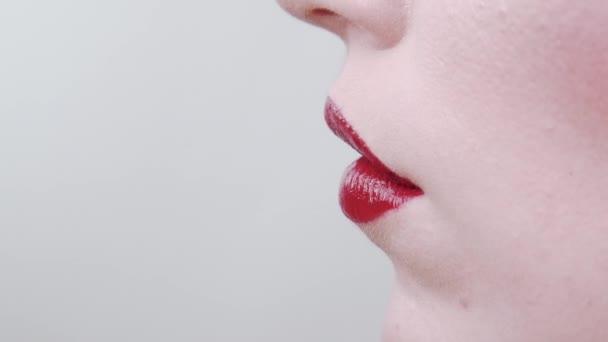 Labbra femminili in primo piano con rossetto rosso. inquadratura di profilo. In studio su sfondo bianco. Saloon di bellezza. Dipinge rossetto rosso abbassare il labbro. Ha un tubo di rossetto tra le mani. nerezza. Pelle pulita.