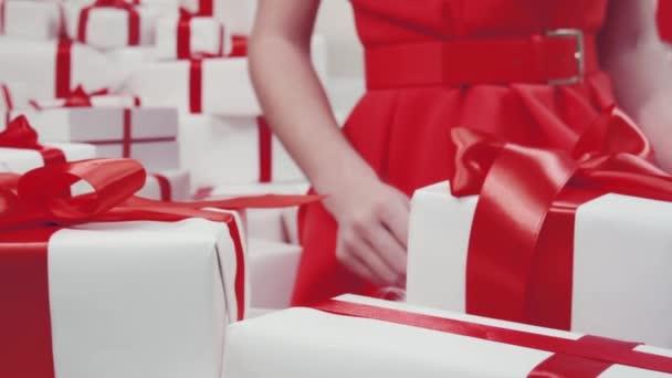 Die fröhliche attraktive Frau im roten Kleid hält ein Geschenk in den Händen und blickt genüsslich in eine Geschenkschachtel. isoliert im Studio auf weißem Hintergrund. Geschenk in der Hand.