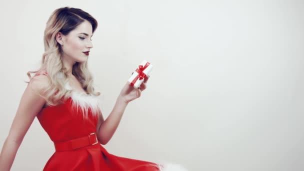 Vidám nő télapó kalapban, ajándékokkal, elszigetelt fehér háttérrel. A piros ruhás lány kezében egy fehér ajándékdoboz van. Lány és szilveszteri ajándékok. Gratulálok a karácsonyhoz. Ajándék a kézben.