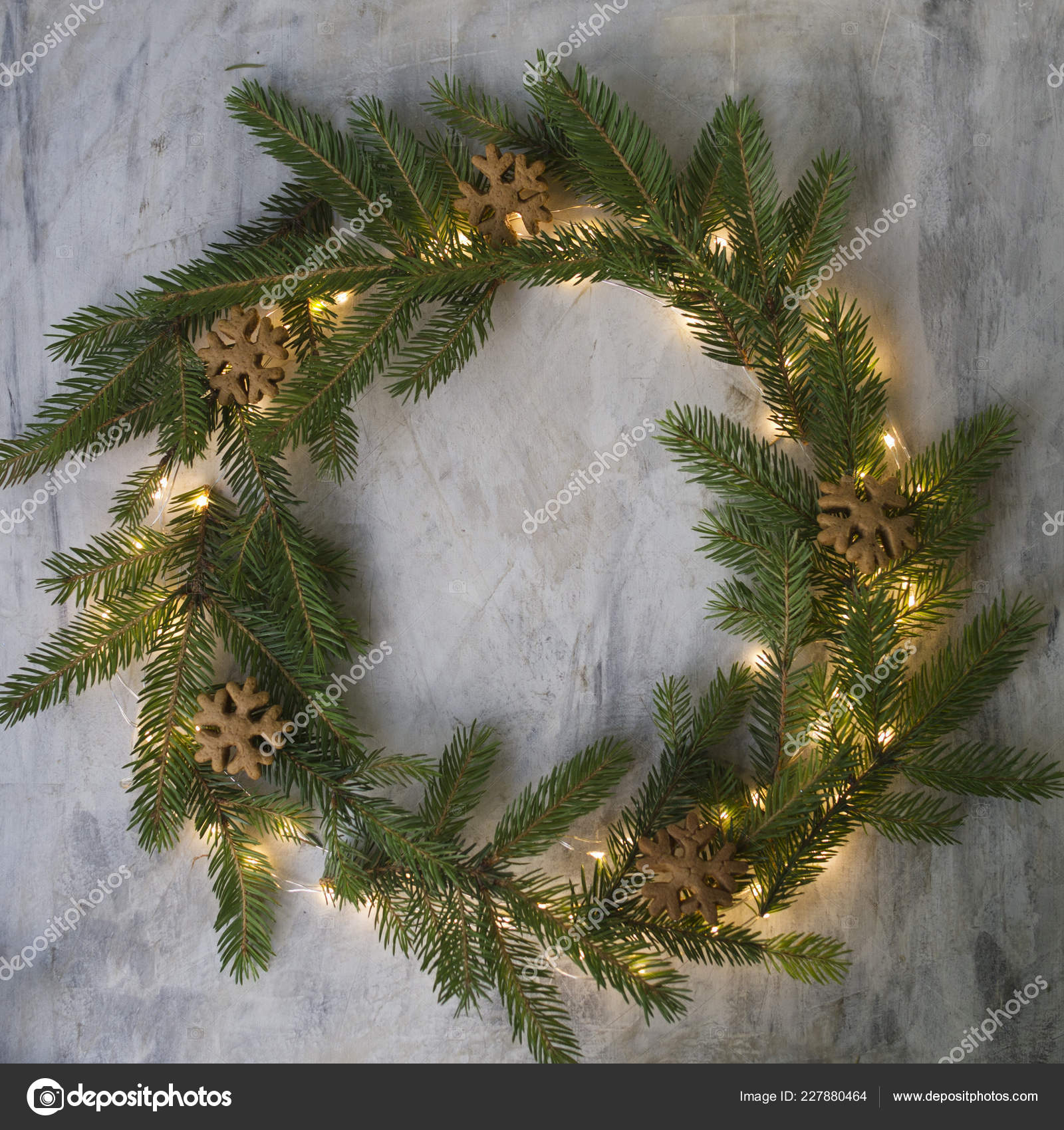 christmas wreath made of fir branches cookies and glowing lights on gray background new year background christmas card flat lay copy space photo by