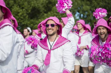 Traena, Norway - July 07 2017: men from the choir Oslo Fagottkor in their pink uniform participating in the Traena gay Pride during Traenafestival, music festival taking place on the small island of Traena