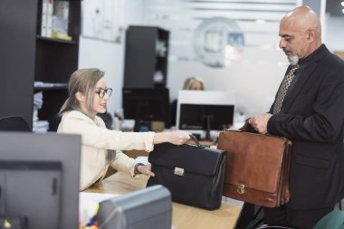 Mature man and young woman with briefcases in office symbolizing changing generations and equality of sex in employment.