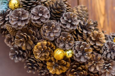 Christmas wreath of fir cones. Christmas balls of gold and pink color. The decor. The wall is covered with wood. Green branches ate. Yalta. Rest in Crimea.