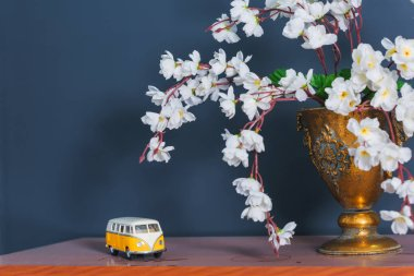 Spring decor. The walls are blue. White flowers in a bronze vase. The interior of the room. Wooden shelf. Decorative element. Toy in the form of a yellow car.