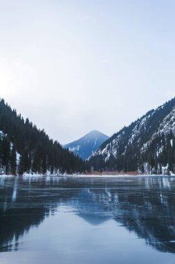 Mountain lake in winter. Ice-covered lake in the mountains. Lake Kolsay in Kazakhstan.