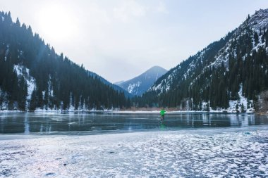 Ice fishing on a mountain lake. Fishing on the frozen surface of the lake. Fisherman on a winter lake.