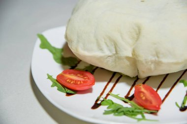 Vegetarian dish. Food without salt and oil. Dish of dough with arugula and tomatoes.