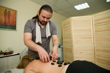 The masseur massages the woman with the help of heated stones. General plan