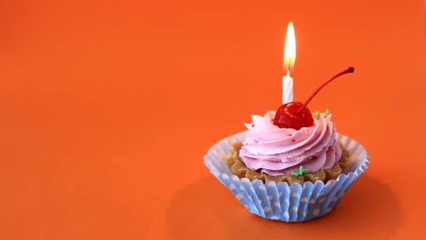 Születésnapi torta meggy, rózsaszín krém és égő gyertya, születésnapi narancssárga háttérrel. Time lapse videó