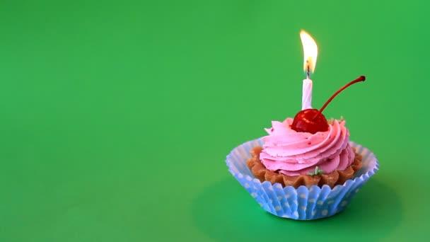 Geburtstagstorte mit Kirsche, rosa Sahne und brennender Kerze zum Geburtstag auf grünem Hintergrund