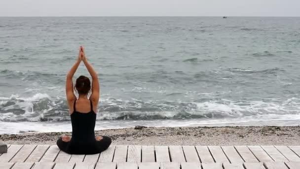 Mladá žena, která dělá jógu u moře ráno