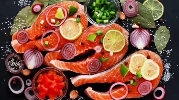 Koch bereitet rohe Stücke von rotem Fischlachs zu, bestreut mit Gewürzen, Sesam, Draufsicht