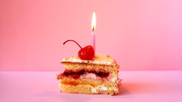 Narozeninový dort s cherry a hořící svíčka k narozeninám na růžovém pozadí. Časosběrné video