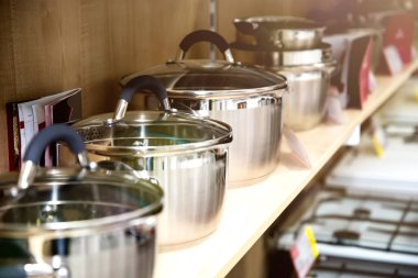 A set of stainless steel utensils on the shelves of the store, close-up.