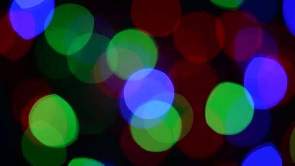 Blikající barevná světla na tmavém pozadí. Zaostřil obraz. Barevná vánoční světla.