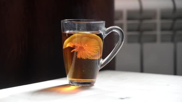 eine transparente Tasse mit heißem Wasser und Zitrone auf dem Hintergrund eines Heizkörpers. die hellen Strahlen der Sonne scheinen durch eine transparente Tasse mit einem Teegetränk.
