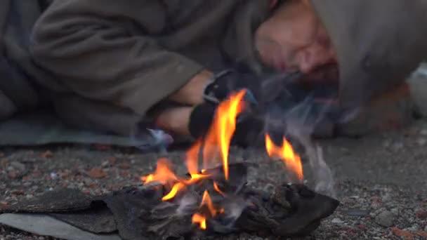 Ein Obdachloser schläft auf der Straße und versucht, sich am Feuer warm zu halten. Der Landstreicher liegt in alten Kleidern auf dem Boden. Der Rauch eines sterbenden Feuers sticht einem Obdachlosen in die Augen... Großaufnahme. Tageslicht.