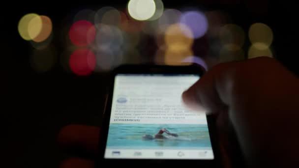 Benutzer scrollt soziales Netzwerk auf einem Smartphone in der Nacht mit defokussierten Stadt Bokeh Lichter im Hintergrund