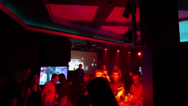 Crowd dancing in night club with live dj performance, neon lights, lasers