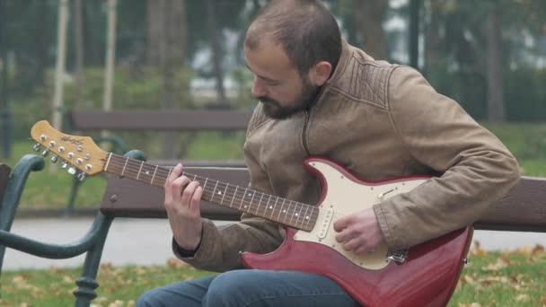 Mladý rockový hudebník procvičující své kytarové dovednosti venku, živé vystoupení, trénink, zdokonalování své hry