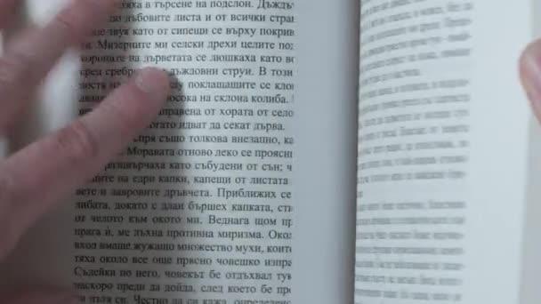 Osoba obrací stránky knihy a čtení