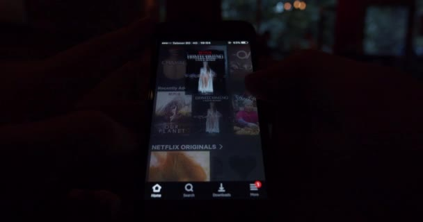 User watching movies on Netflix application from a smartphone - streaming video concept