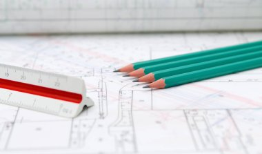 Architectural plans lying on drawing board with green pencils