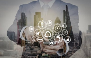 Sustainable development with icons of renewable energy and natural resources preservation with environment protection inside connected gears.Double exposure of success businessman using smart phone with abstract building.