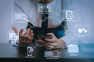 Developing programming and coding technologies with Website design in virtual diagram.businessman working with smart phone on wooden desk in modern office with glass reflected view
