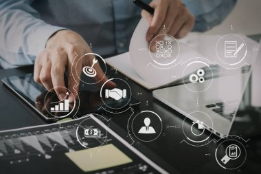 Business process management with workflow automation diagram and gears in virtual flowchart.businessman working with smart phone and digital tablet and laptop computer  on wooden desk in modern office.