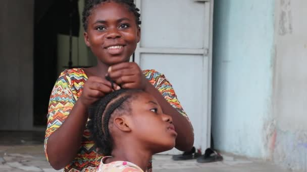 abidjan, Ivory Coast - June 26, 2018: Little girls sitting in front of her parents house braid her little sister sitting in front of her
