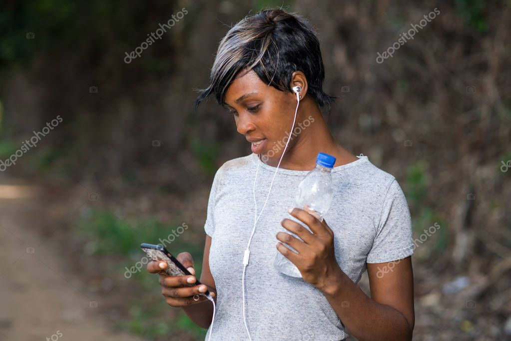 Young woman in sportswear listening to music in headphones