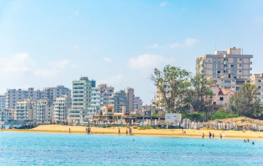 People are enjoying a sunny day on a beach in front of Varosia district of Famagusta, Cypru