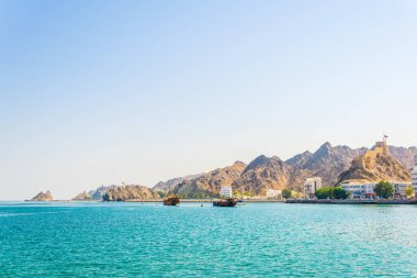 a pair of dhows - traditional arab ships - is heading to the sea from Muttrah part of Muscat dominated by a fort on a hill, Oman.