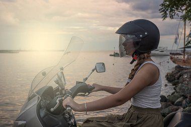 Girl on a scooter by the sea, sunset