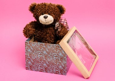 Gift box with a teddy bear inside, pink background