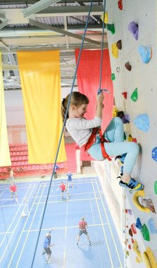 Healthy lifestyle concept: active caucasian female child is on the climbing wall