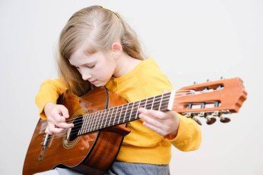 Pretty little girl playing acustic guitar