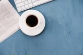 Ranní káva a čerstvé noviny na modré stolní deska.