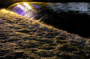 Rays of light reflected in the night river