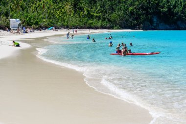 SAINT THOMAS - JAN 2018: People relax on a wonderful beach with white sand and azure water on a tropical island.