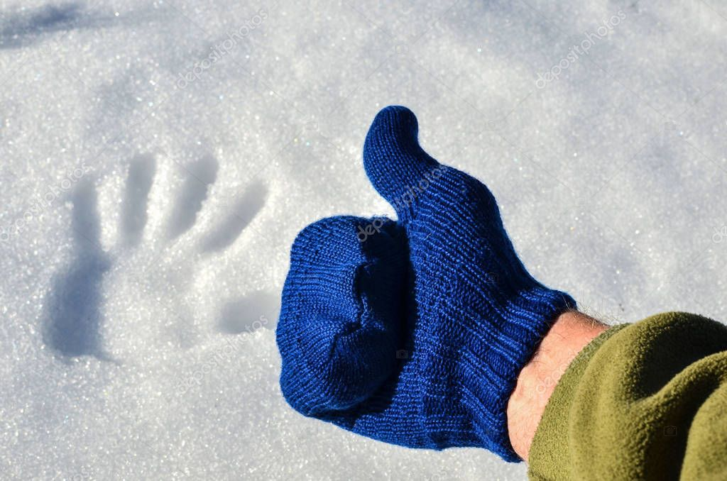 Blue knitted wool mitten, thumb up, on a background of white snow with a fingerprint. The concept of the onset of winter or spring, cold or warm
