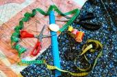 Grundlagen des Messens und Schneidens von Textilien oder feinem Tuch. Arbeitstisch eines Schneiders: Lineal, Muster, Schere, Faden, Nadel, Tuch, Zeichenwerkzeug, Fingerhut. Schneiderei-Werkzeuge