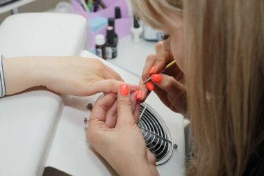 Manicure. Master make nail extension: drawing of white gel on free edge of a nail
