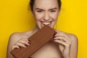 Boldog fiatal nő élvezi eszik csokoládét, a sárga háttér