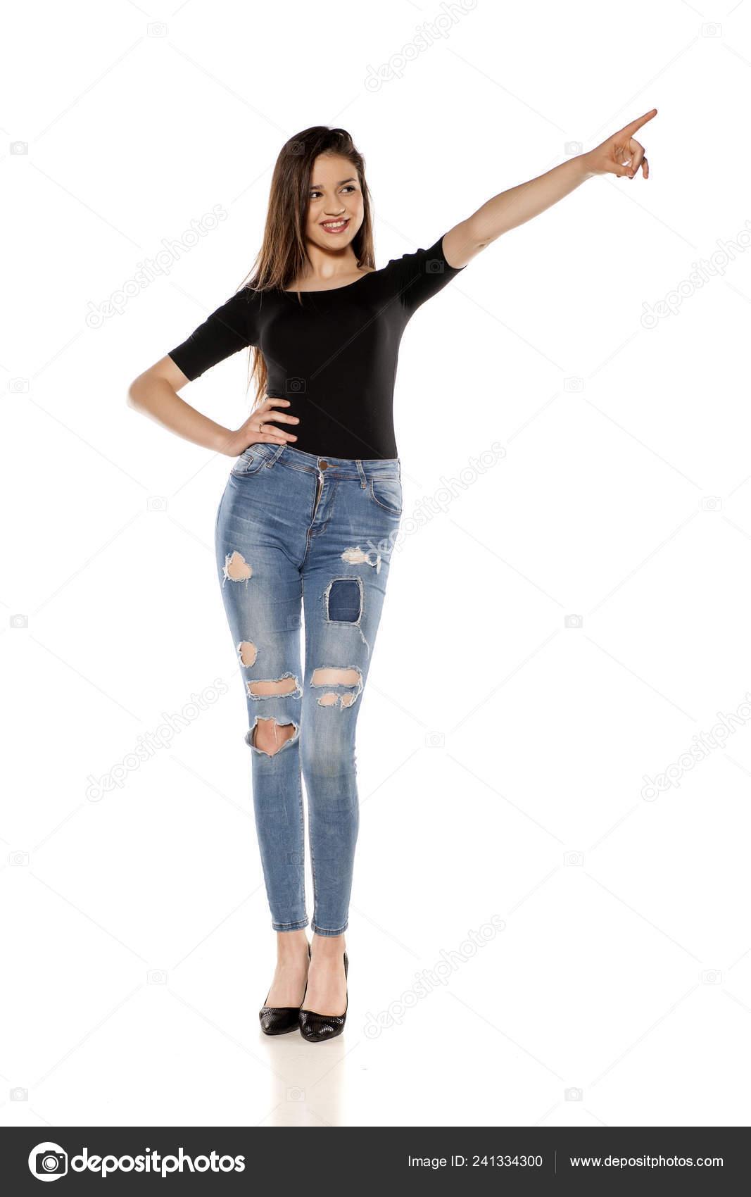 167349490849 Ευτυχισμένος Νεαρό Κορίτσι Στο Σχισμένο Τζιν Κατάδειξης Λευκό Φόντο– εικόνα  αρχείου