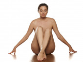 sensual portrait of a naked woman sitting on the floor