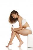 Junge Frau cremt ihre Beine auf weißem Hintergrund ein