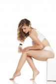 Junge hübsche Frau cremt ihre Beine auf weißem Hintergrund ein